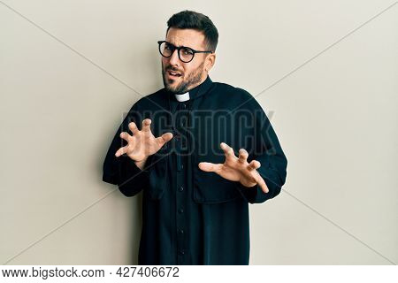 Young hispanic man wearing priest uniform standing over white background disgusted expression, displeased and fearful doing disgust face because aversion reaction. with hands raised