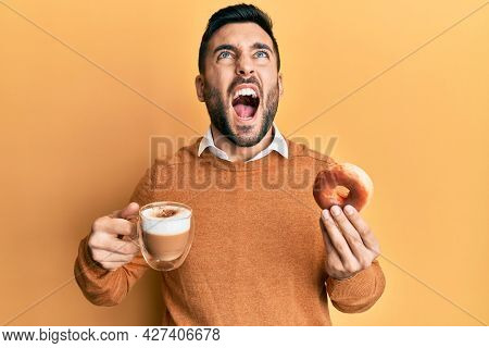 Young hispanic man eating doughnut and drinking coffee angry and mad screaming frustrated and furious, shouting with anger looking up.