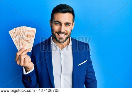 Young hispanic businessman wearing business suit holding turkish lira banknotes looking positive and happy standing and smiling with a confident smile showing teeth