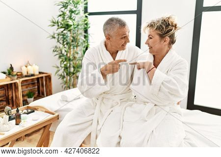 Middle age caucasian couple wearing bathrobe at wellness spa smiling happy pointing with hand and finger