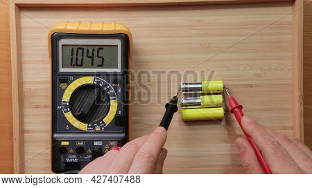 Testing AA battery cells with digital multimeter tool, voltage check showing low value, battery is used and mostly discharged