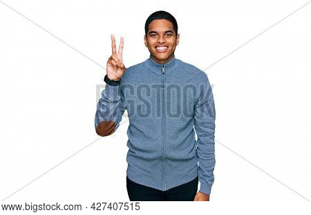 Young handsome hispanic man wearing casual sweatshirt showing and pointing up with fingers number two while smiling confident and happy.