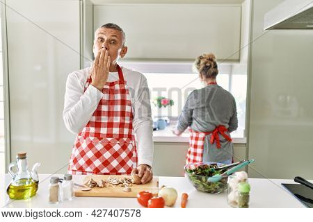 Middle age caucasian couple cooking healthy salad covering mouth with hand, shocked and afraid for mistake. surprised expression