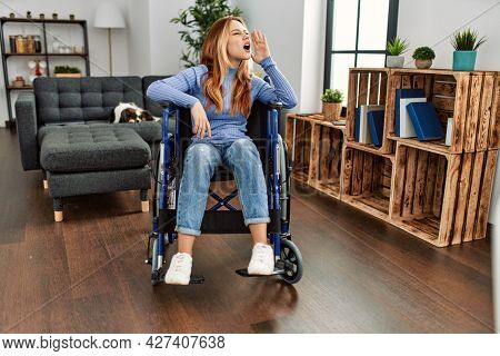 Young beautiful woman sitting on wheelchair at home shouting and screaming loud to side with hand on mouth. communication concept.