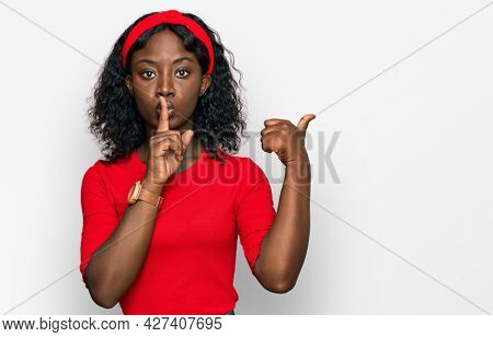 Beautiful african young woman wearing casual clothes asking to be quiet with finger on lips pointing with hand to the side. silence and secret concept.