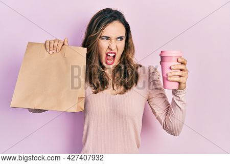 Young hispanic girl holding take away paper bag and coffee angry and mad screaming frustrated and furious, shouting with anger. rage and aggressive concept.