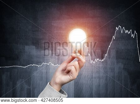 Business Woman Hand With Glowing Incandescent Lamp On Background Grunge Wall. Successful Business So