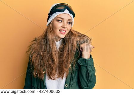 Beautiful blonde caucasian woman wearing snow wear and sky glasses smiling with happy face looking and pointing to the side with thumb up.