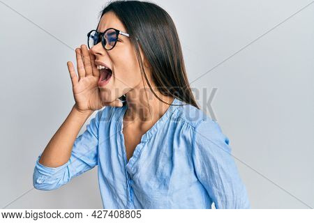 Young hispanic girl wearing casual clothes and glasses shouting and screaming loud to side with hand on mouth. communication concept.