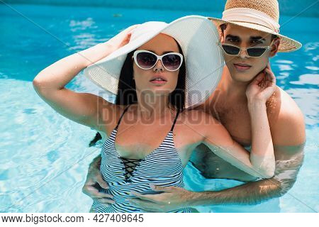 Man In Sun Hat And Sunglasses Looking At Camera While Embracing Girlfriend In Swimming Pool