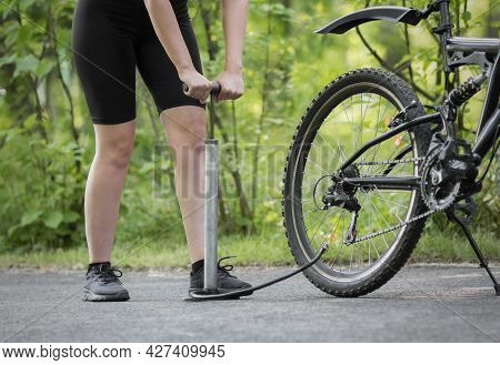 A Girl Pumps A Bicycle Wheel With A Pump. Bicycle Repair In The Forest. Close Up