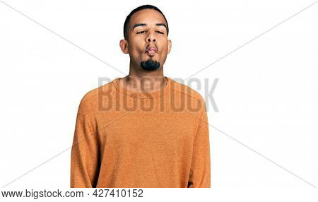 Young african american man wearing casual clothes making fish face with lips, crazy and comical gesture. funny expression.