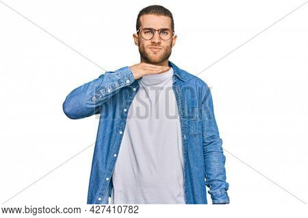Young caucasian man wearing casual clothes cutting throat with hand as knife, threaten aggression with furious violence