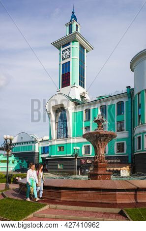 Novosibirsk, Russia - 20 July, 2021: Clock tower and fountain square of suburban train station