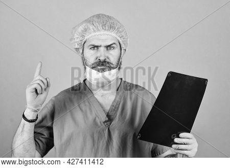 Diagnose Patient Injury. Man Look At Roentgen. Radiologist Hold Xray. Surgeon Doctor Examines Radiog
