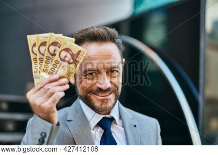 Middle age businessman smiling happy holding hungarian forint banknotes at the city.