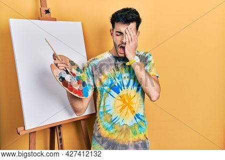Young hispanic man standing drawing with palette by painter easel stand yawning tired covering half face, eye and mouth with hand. face hurts in pain.