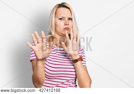 Young caucasian woman wearing casual clothes moving away hands palms showing refusal and denial with afraid and disgusting expression. stop and forbidden.