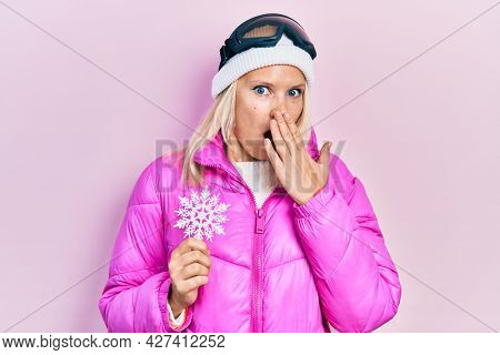 Beautiful caucasian blonde woman wearing snow wear and sky glasses holding snowflake covering mouth with hand, shocked and afraid for mistake. surprised expression
