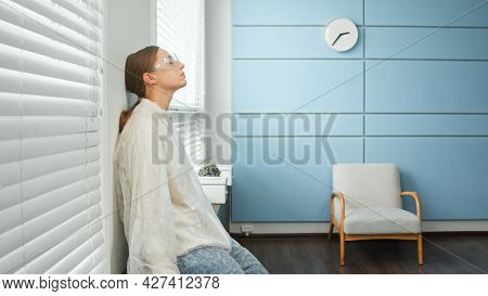 Tired young woman physician therapist in white sterile coat blue mask and glasses sits on designed windowsill leaning on wall in hospital room