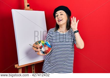 Middle age hispanic woman standing drawing with palette by painter easel stand waiving saying hello happy and smiling, friendly welcome gesture