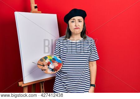 Middle age hispanic woman standing drawing with palette by painter easel stand depressed and worry for distress, crying angry and afraid. sad expression.