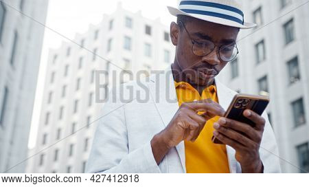 Black man in suit with hat types on smartphone and laughs cheerfully standing by office buildings under bright sunlight close view