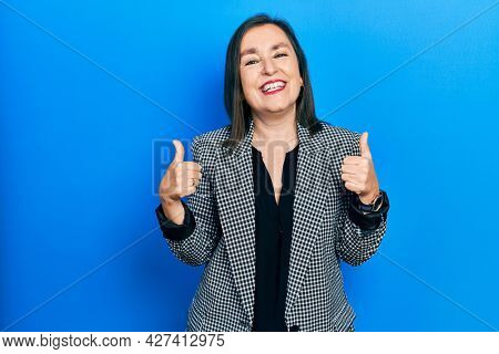 Middle age hispanic woman wearing business clothes success sign doing positive gesture with hand, thumbs up smiling and happy. cheerful expression and winner gesture.