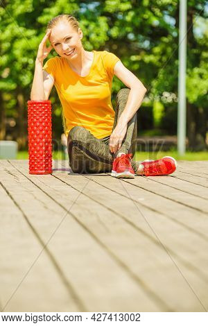 Young Woman Exercises In Park, Using Gym Accessory, Foam Roller For Muscle Massage. Staying Fit And