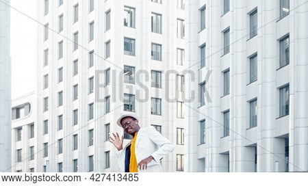 Amazed black guy in yellow t shirt and white suit dances contemporary dance against megalopolis office buildings lit by sunlight