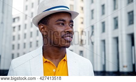 Thoughtful man in yellow t shirt and white classic suit with hat looks around standing on street with highrise buildings closeup