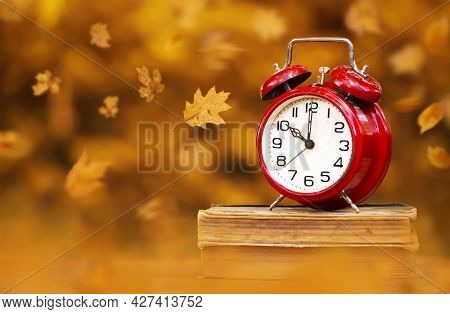 Red Clock On Books With Leaves. Back To School In Autumn, Daylight Savings Time Background.