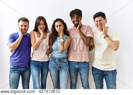 Group of young people standing together over isolated background touching mouth with hand with painful expression because of toothache or dental illness on teeth. dentist concept.