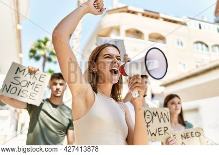 Group of young hispanic activists protesting holding banner and using megaphone at the city.