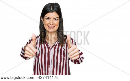 Beautiful brunette woman wearing striped shirt approving doing positive gesture with hand, thumbs up smiling and happy for success. winner gesture.