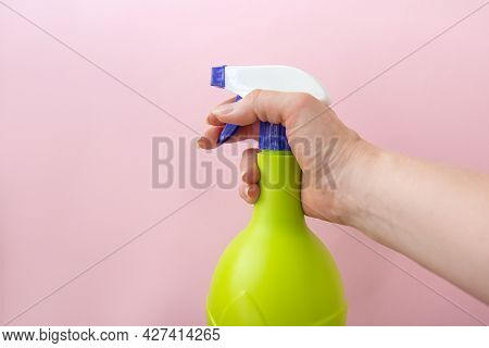 Hand Holding Plastic Spray Yellow Bottle Isolated On Pink Background. Bottle For Detergent Or For Pl