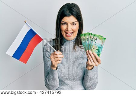 Young hispanic woman holding russia flag and rubles banknotes smiling and laughing hard out loud because funny crazy joke.
