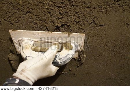 Male Hand With Trowel Plastering The Wall With Cement Mortar