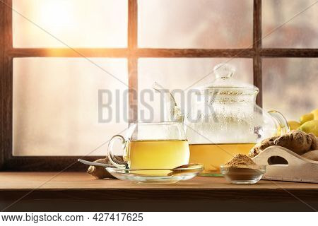 Hot Ginger-infused Mug On A Windowsill Next To A Teapot And Ginger Root. Front View.