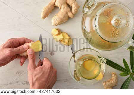 Man Preparing Ginger Infusion On A White Table With Sliced Ginger Root And Teapot. Top View.