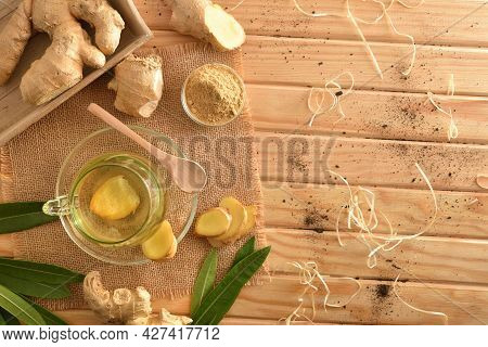 Organic Ginger Infusion On Wooden Table In The Field With Root Ginger Powder Leaves Straw And Soil.