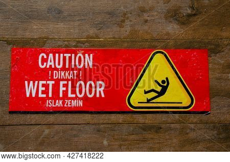 Red Warning Sticker For Wet Floor On Brown Tiled Floor. The Inscription On Red Information Sticky La
