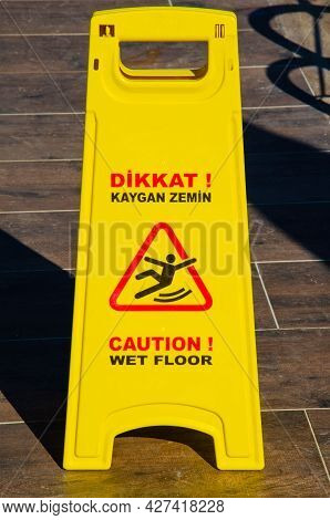 The Inscription On Yellow Information Plate Caution Slippery Floor In The Hotel In Turkish