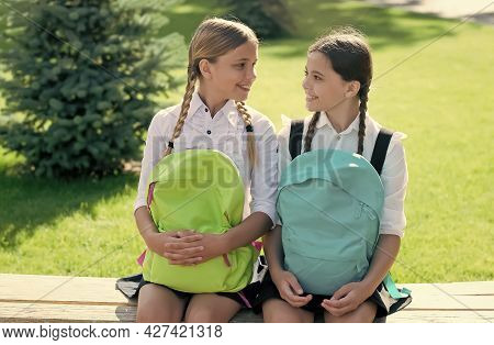 Happy School Friends In Formal Uniform Sit On Park Bench Holding Bags After School Day Sunny Outdoor