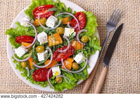 Warm Salad With Pumpkin, Feta Cheese, Sun-dried Tomatoes, Olives, Arugula And Red Onion. Close-up.