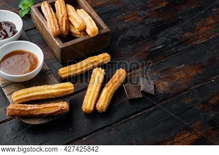 Churros With Caramel, Traditional Spanish Cusine, On Old Dark  Wooden Table Background With Space Fo
