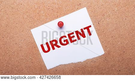 White Paper With The Text Urgent Is Attached To The Wooden Background With A Red Button.