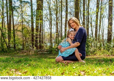 A beautiful expectant mother poses with her little daughter in an outdoor environment