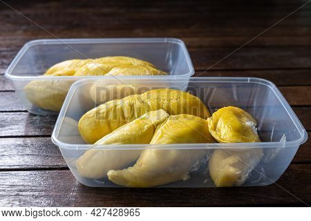 Golden Yellow Musang King Durian Pulp Flesh In Two Containers On Wooden Surface