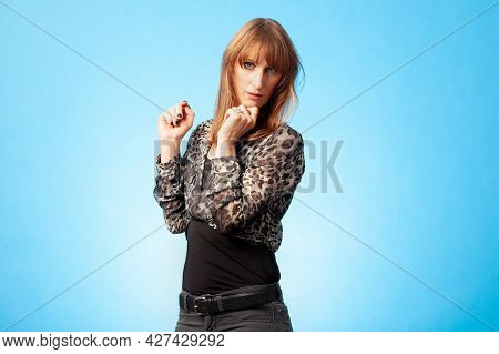 Portrait Of An Attractive Brunette Woman Wearing A Blouse With A Leopard Animal Print Against A Blue
